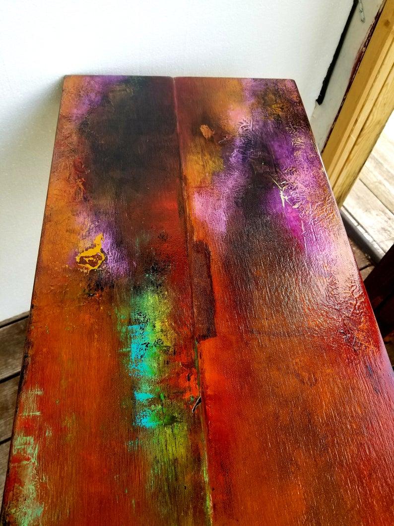 прихотливы фанки металлический окрашенный стол, оранжевый и фиолетовый огонь опал аннотация на дереве. ноги лапы ноги трубы металлической промышленной